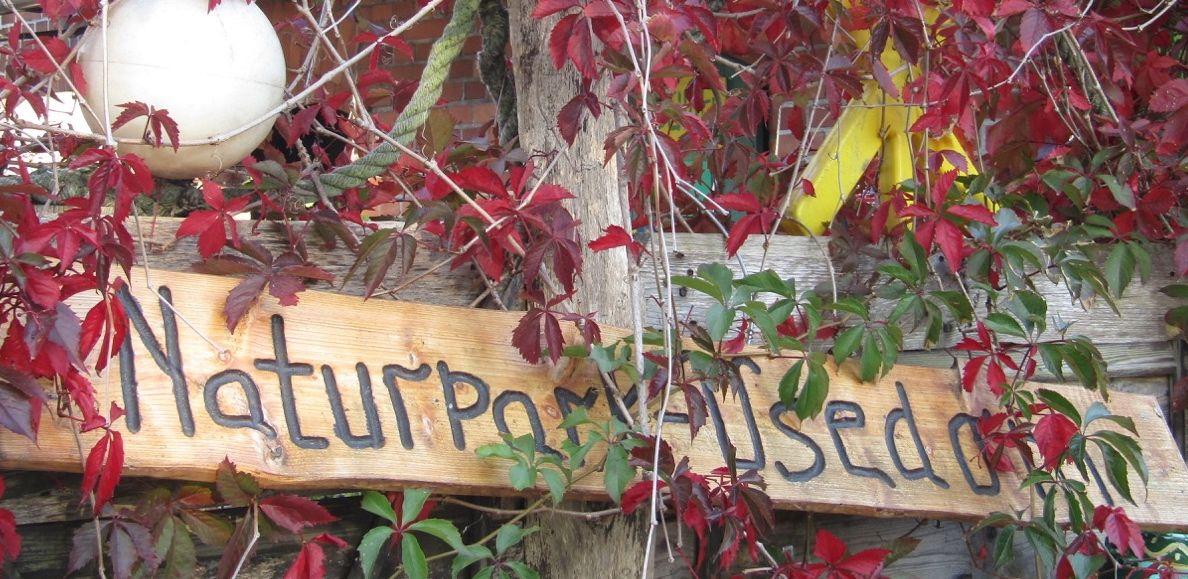 Ein Holzschild sagt wie der Naturpark heisst.